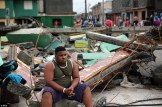 A man looks pensive as he sits atop a pile of rubble after the hurricane wreaked destruction in Cuba yesterday