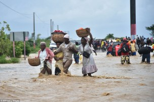 A family clings hold of one another as they try to cross the over flowing Rouyonne river in Haiti where residents began the messy and probably grim task of assessing the storm's toll