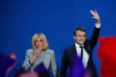French centrist presidential candidate Emmanuel Macron waves as his wife Brigitte gestures before he addresses his supporters at his election day headquarters in Paris , Sunday April 23, 2017. Macron and far-right populist Marine Le Pen advanced Sunday to a runoff in France's presidential election, remaking the country's political system and setting up a showdown over its participation in the European Union. (AP Photo/Christophe Ena)